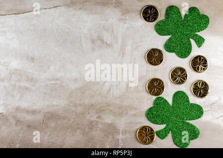 Deux trèfles cuir vert avec des pièces d'or sur fond beige de pierres naturelles. Vue d'en haut. Copier l'espace. Banque D'Images