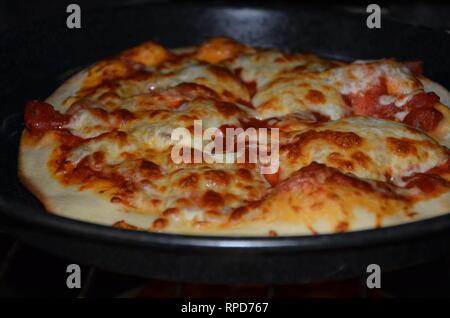 Pizza fraîche la cuisson au four, restauration rapide Banque D'Images