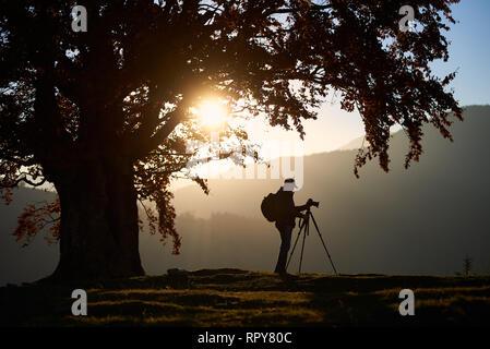Profil de l'homme voyageur sac à dos avec trépied photo au soleil couchant lumineux éclairé par en bleu ciel debout sur fond de vallée verdoyante sur beauti Banque D'Images