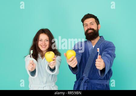 Brosser les dents concept. L'hygiène buccale. Dans deux peignoirs tenir des brosses à dents et les pommes. L'homme au féminin l'hygiène. Première règle d'hygiène personnelle. Couple in love nettoyer les dents tous les matins. Sourire en santé. Banque D'Images