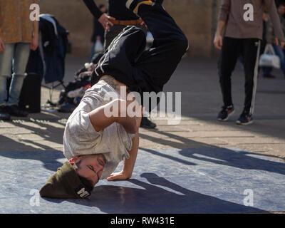 16 février 2019, Bologne, Italie. Certains garçons break dance danse au milieu d'une rue de Bologne, en Italie et en face d'une église. Banque D'Images