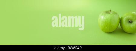 Pomme verte fraîche parfait isolé sur fond vert avec wate Banque D'Images