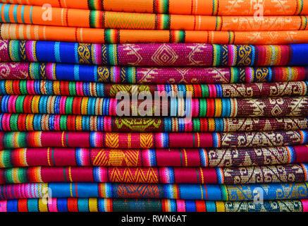 Pile de textiles colorés sur le marché indigène d'Otavalo, Équateur. Ces textiles peuvent être trouvés dans le monde andin: Pérou, Bolivie, Équateur. Banque D'Images