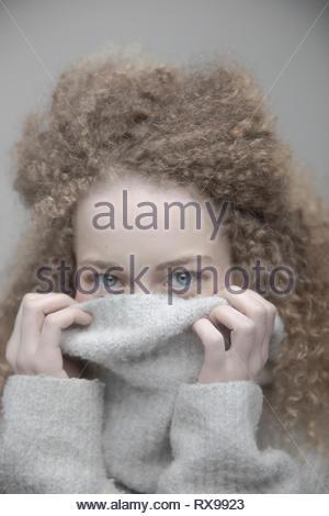 Belle petite blonde espiègle portrait femme aux longs cheveux bouclés se cachant dans sweater Banque D'Images