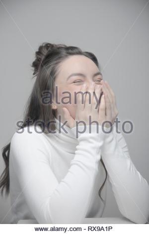 Belle jeune femme espiègle Portrait Laughing with head in hands Banque D'Images