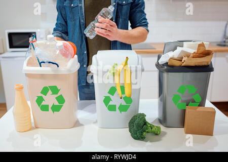 Le tri des déchets à la maison. Le recyclage. Man putting bouteille plastique dans la poubelle dans la cuisine Banque D'Images