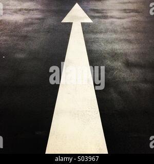 Flèche blanche longue peints sur l'asphalte. Banque D'Images