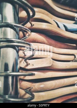 Cintres en bois sur un rail suspendu d'un rack de vêtements Banque D'Images