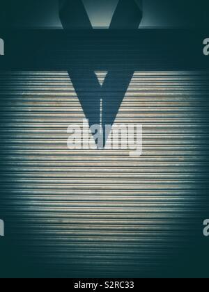 L'ombre en forme de flèche sur une grande porte industrielle en métal. Banque D'Images