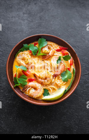 Soupe Laksa. Soupe de crevettes et nouilles laksa sur fond noir, vue du dessus, copiez l'espace. Malaise d'aliments asiatiques. Banque D'Images
