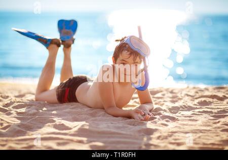 Enfant allongé sur la plage avec un masque de natation Banque D'Images