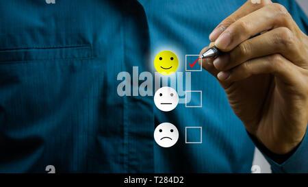 Le client conceptuel a répondu à l'enquête. Le client a l'aide de part choisissez icône sourire happy face à l'écran. Montre que le client est très satisfait Banque D'Images