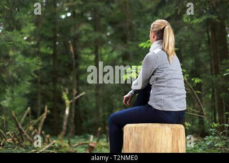 Une femme détendue sur un tronc d'arbre dans une forêt Banque D'Images