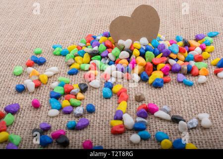 Coeur de papier au milieu des cailloux colorés sur toile sol Banque D'Images