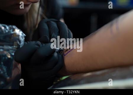 Femme artiste de tatouage en donnant un tatouage. Faire un tatouage Banque D'Images