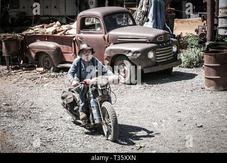 Old Timer barbu rides anciennes en face de vieux camion à plateau Banque D'Images