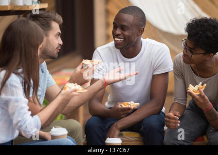 Heureux multiraciale friends laughing at blague eating pizza in cafe Banque D'Images