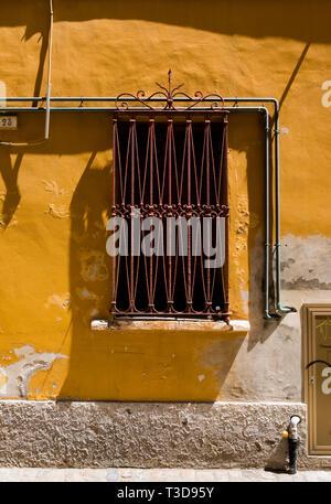 Détail d'une grille rouillée, fenêtre ouvragée et mur de plâtre jaune dans les rues de Fano, Italie Banque D'Images