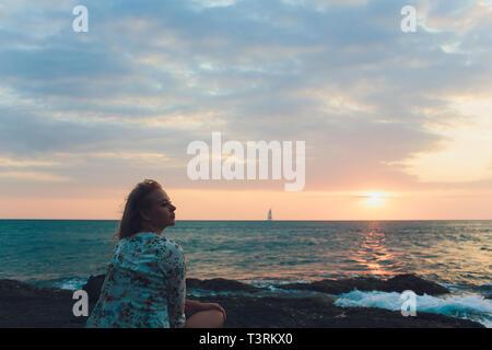 Profiter de vacances. Jeune couple voyageur sur le coucher du soleil sur la mer. Banque D'Images