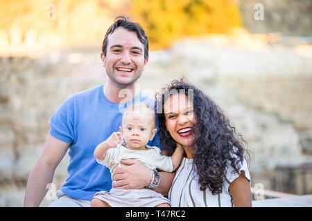 Jeune couple heureux bénéficiant de temps avec petit bébé garçon, père et fils avec le rouge à lèvres imprime sur leur front, Pologne Banque D'Images