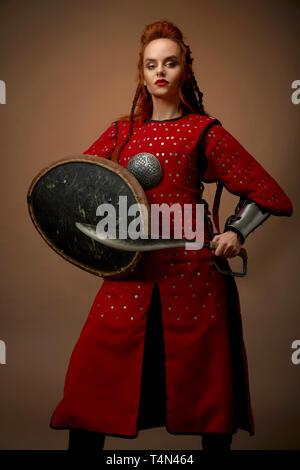 Sérieux, courageux comme héros noble femme portant en rouge tunique moyenâgeuse. Beau, charmant modèle avec ginger hair holding shield et poignard, posing in studio avec arme. Banque D'Images