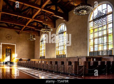 La lumière qui brillait à travers les fenêtres Renaissance mission historique, Union Station, à Los Angeles, avec des luminaires Art déco ancien suspendues au-dessus de la billetterie. Banque D'Images