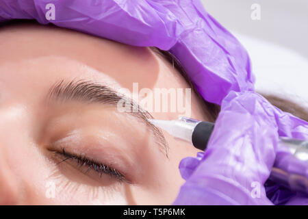 Faire Cosmetologist maquillage permanent sur les sourcils. Tatoueur avec gants et violet instrument professionnel l'application de tatouage en studio de beauté Banque D'Images