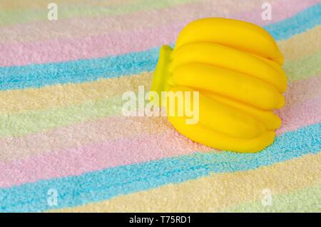 Savon aroma bio en forme de banane sur une serviette multicolore. Soins de beauté concept. Copy space Banque D'Images