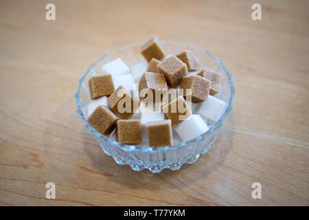 Cubes de sucre brun et blanc des morceaux de sucre dans un bol en verre. Banque D'Images