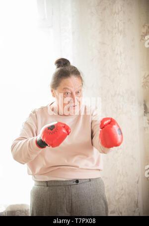 Une vieille femme en rouge des gants de boxe est prêt à se battre Banque D'Images