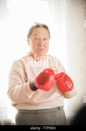 Une vieille femme au pull et gants de boxe est prêt à se battre Banque D'Images