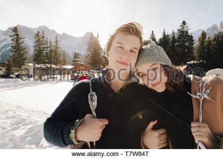 Portrait heureux, young couple at frozen ice skating pond Banque D'Images