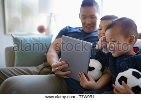 Père et fils using digital tablet sur salon canapé Banque D'Images