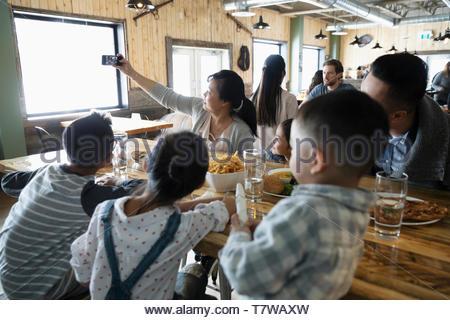 Famille avec le téléphone appareil photo en tenant en selfies restaurant Banque D'Images