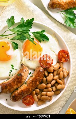 Close up de petit-déjeuner avec les œufs, saucisses, tomates, haricots verts, sur la plaque. Vue d'en haut Banque D'Images