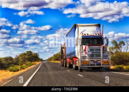 Mighty long road de chariot en mouvement du fret à travers l'Australie sur une autoroute vide solitaire en milieu rural , de l'outback. Banque D'Images