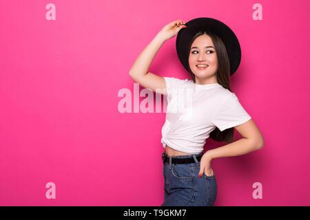 Charmante asian woman in black hat standing sur fond rose. Banque D'Images