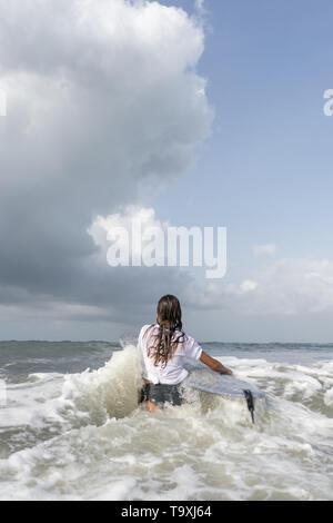 Surfeur Femme en blanc T-shirt entre dans l'océan. Banque D'Images