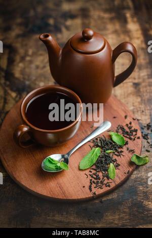 Thé à la menthe dans la théière et tasse en céramique marron sur un fond de bois chaud avec thé et les feuilles de menthe. Banque D'Images