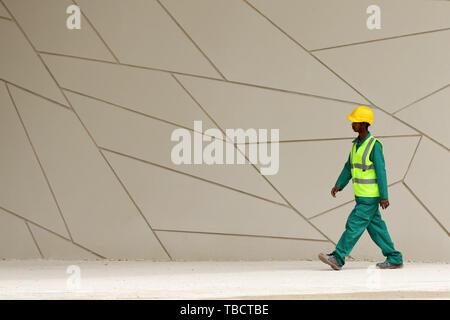 Doha, Qatar - 11 avril, 2019: un travailleur avec un uniforme et un vêtements de promenades dans le Musée national du Qatar. Banque D'Images