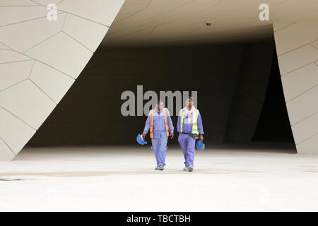Doha, Qatar - 11 avril, 2019: deux travailleurs en uniforme avec des casques à pied autour du Musée national du Qatar. Banque D'Images