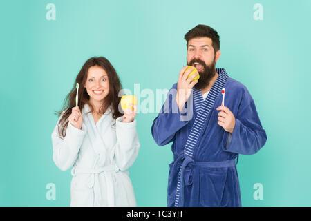 De saines habitudes de vie. Brosser les dents tous les matins. L'hygiène buccale. Deux peignoirs tenir des brosses à dents et les pommes. L'hygiène personnelle. Couple in love nettoyer les dents. La fraîcheur et la propreté. Maintenir les dents en bonne santé. Banque D'Images
