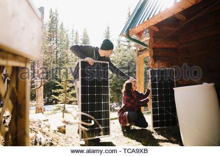 Couple l'installation de panneaux solaires à l'extérieur de cabine Banque D'Images