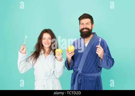 L'hygiène personnelle. Couple in love nettoyer les dents. La fraîcheur et la propreté. Maintenir les dents en bonne santé. De saines habitudes de vie. Brosser les dents tous les matins. L'hygiène buccale. Deux peignoirs tenir des brosses à dents et les pommes. Banque D'Images