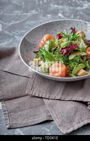 Salade de saumon aux épinards, mâche, épinards, basilic et menthe fraîche. La nourriture faite maison. Concept pour un repas sain et savoureux. Pierre sombre contexte Banque D'Images