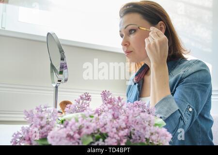 Portrait de femme d'âge moyen avec un miroir de maquillage, belle femme de 40 ans assis à la maison à la table, avec des fleurs lilas Banque D'Images