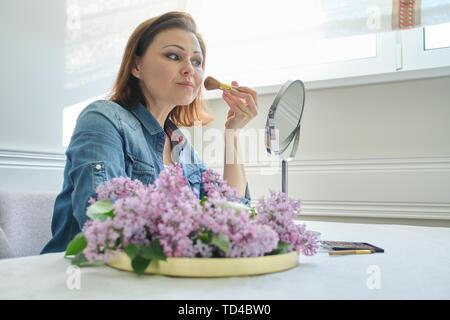 Portrait de femme mature avec un miroir de maquillage, belle femme de 40 ans assis à la maison à la table, avec des fleurs lilas Banque D'Images