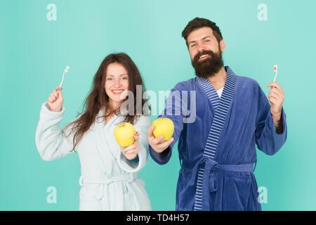 Couple in love nettoyer les dents. La fraîcheur et la propreté. Maintenir les dents en bonne santé. De saines habitudes de vie. Brosser les dents tous les matins. L'hygiène buccale. Deux peignoirs tenir des brosses à dents et les pommes. L'hygiène personnelle. Banque D'Images