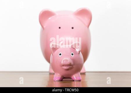 Grandes et petites tirelires rose représentant parent avec enfant. Banque D'Images