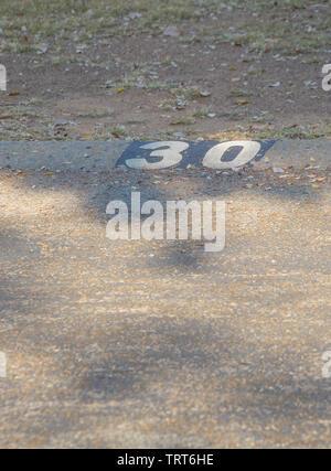Numéro de rue trente peints sur un muret de pierre a diminué avec le temps libre dans le format portrait with copy space Banque D'Images